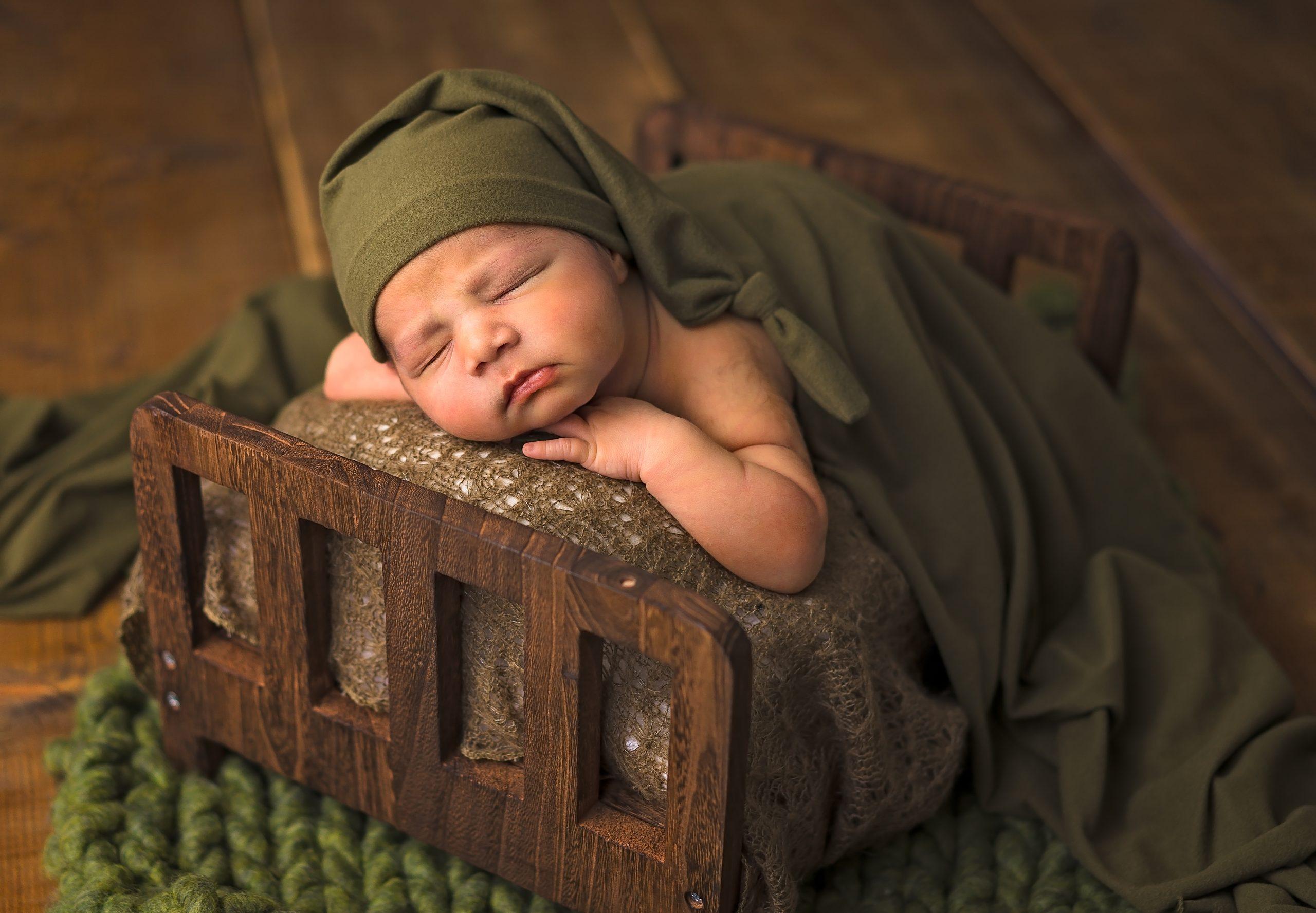 Newborn Baby Sleeping on a Bed with Green Sleeping Cap